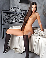 Slender brunette Natalia taking off her clothes on the bed